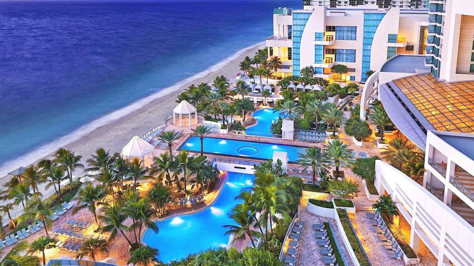 Beach and series of swimming pools at Florida resort hotel