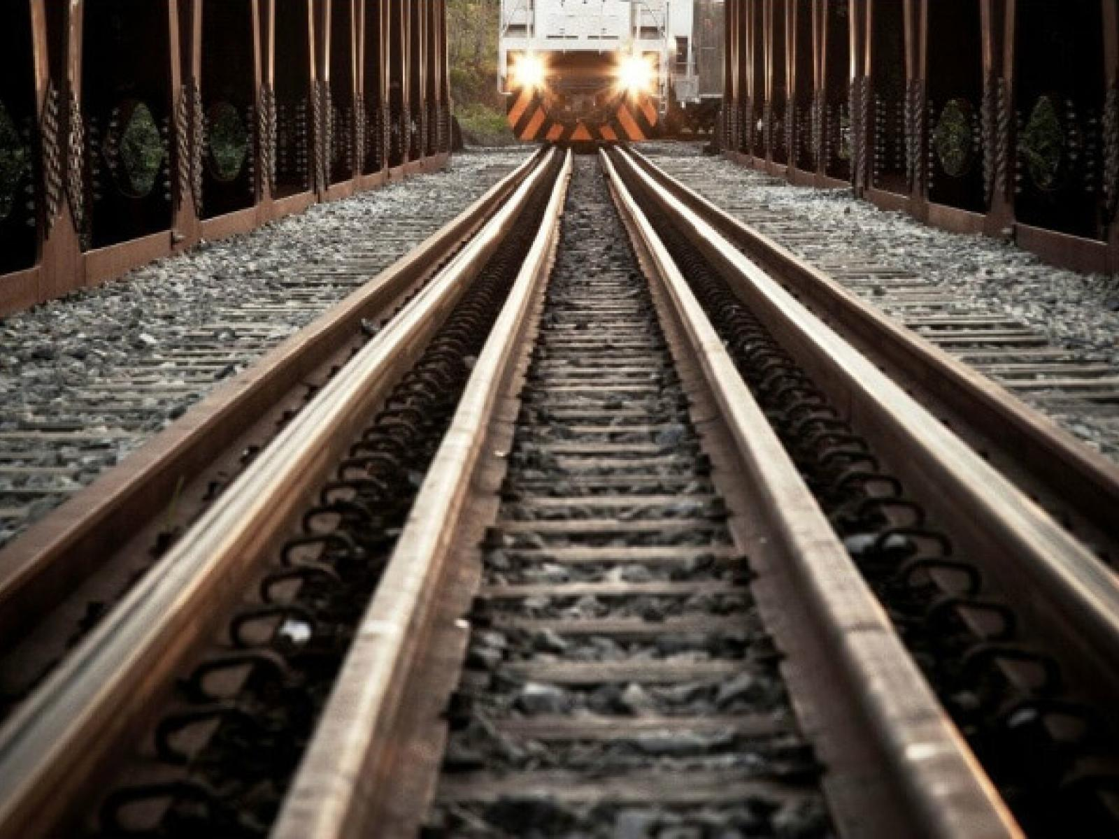 Closeup of railroad tracks with oncoming train in distance