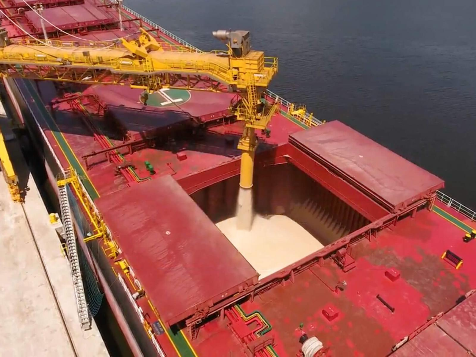 Tanker ship being loaded with sand-colored raw material at portside