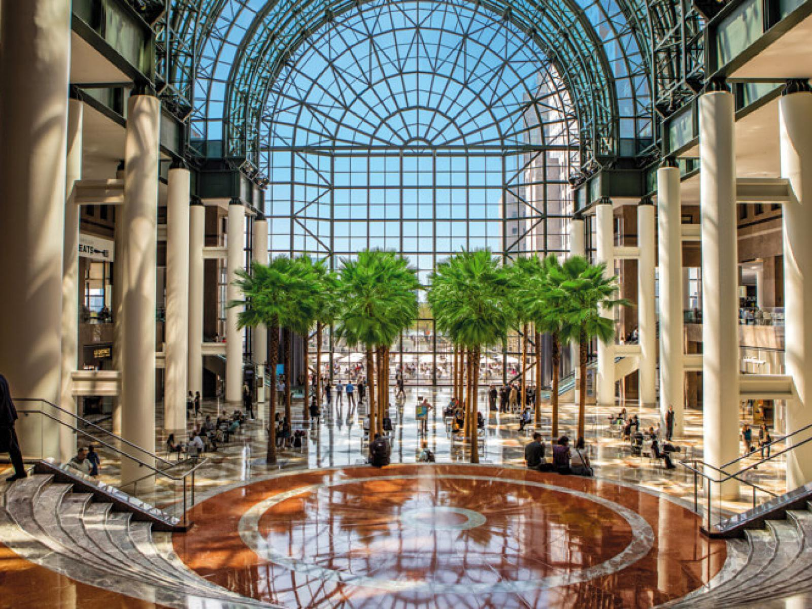 Trees, glass atrium windows and coral-colored marble floors in the Winter Garden