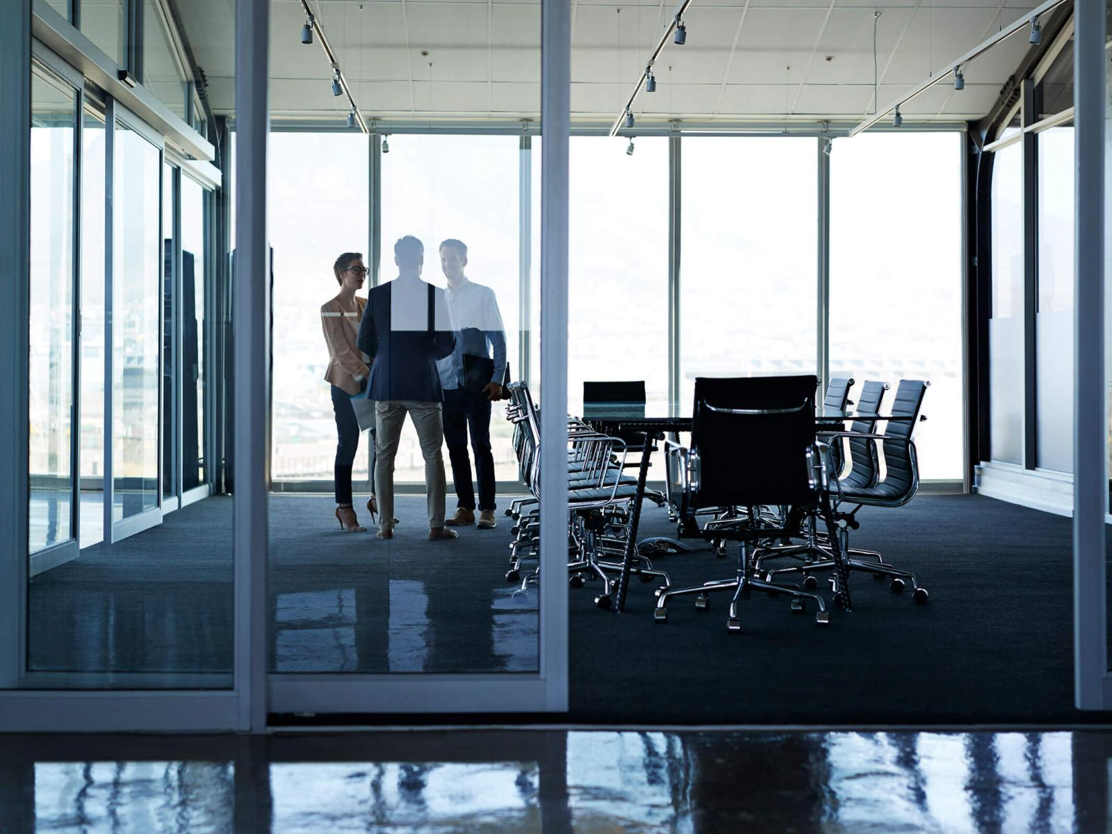 Three office workers talking in conference room