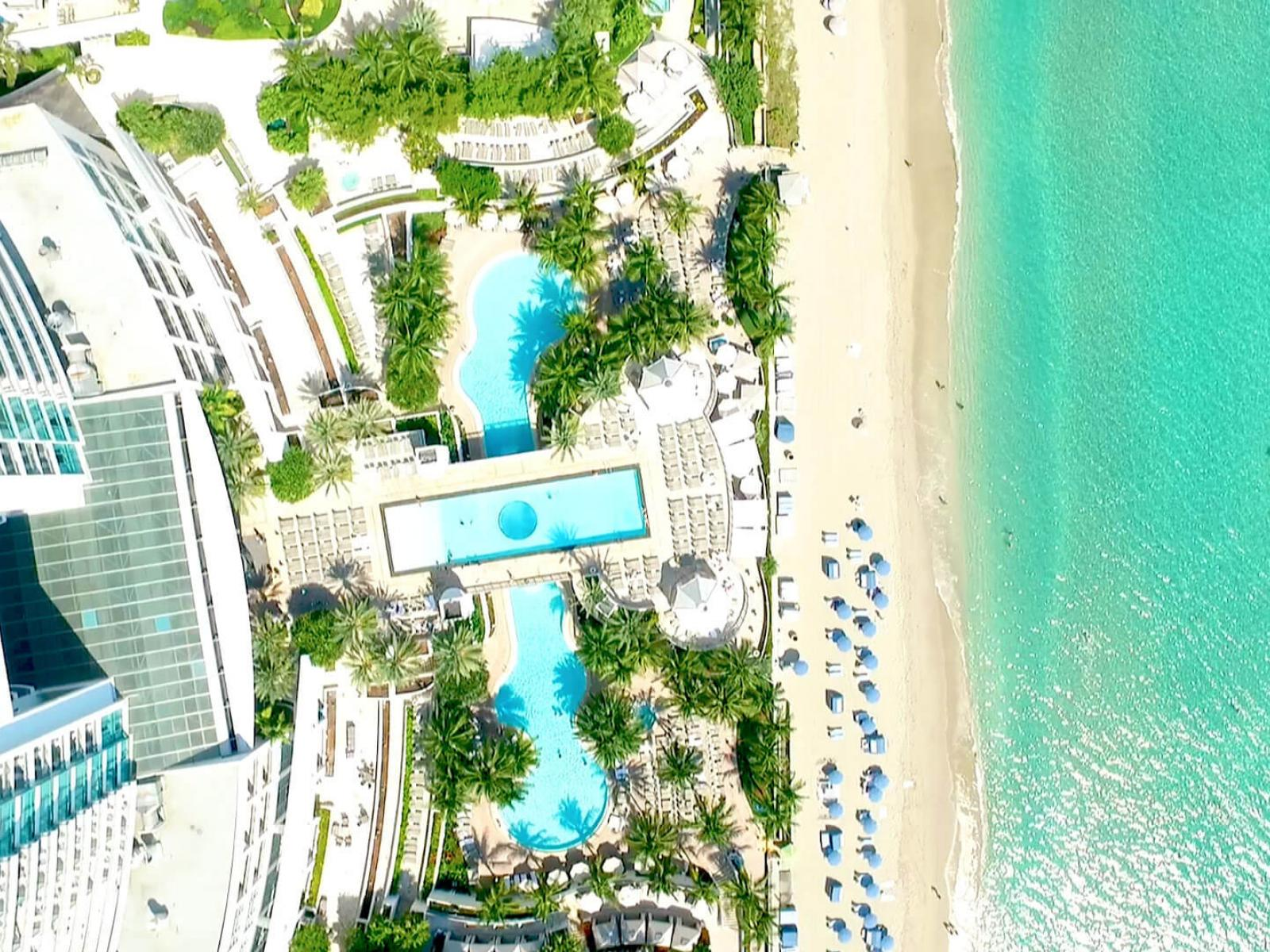Aerial view of beach, swimming pools and hotel façade
