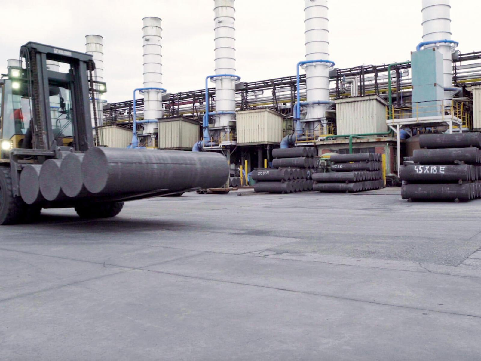 Forklift moving graphite electrodes across exterior factory yard